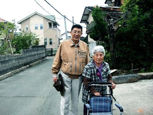 本震後 外の雨漏りがする仮設駐車場で寝泊まりする北野礼子さん(82歳) 惣領 2016年4月18日